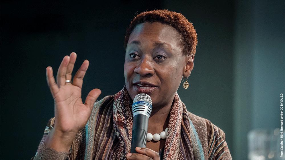 Portrait von Prof. Dr. Maisha-Maureen Auma. Sie hält in ihrer linken Hand ein Mikrofon. Die rechte Hand ist auf Schulterhöhe und untermalt evtl. das Gesprochene.
